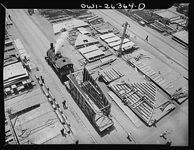 Bethlehem-Fairfield shipyards, Baltimore, Maryland. Locomotive pulling a steel section on a flatcar
