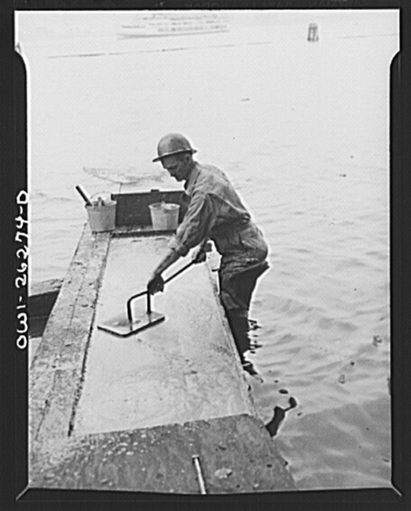 Bethlehem-Fairfield shipyards, Baltimore, Maryland. Preparations for launching a ship. Preparing the shipways with tallow