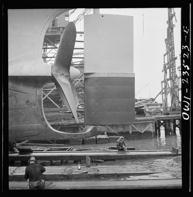 Bethlehem-Fairfield shipyards, Baltimore, Maryland. Propeller and rudder just before a launching. Below, workmen are greasing the outboard end of the ways