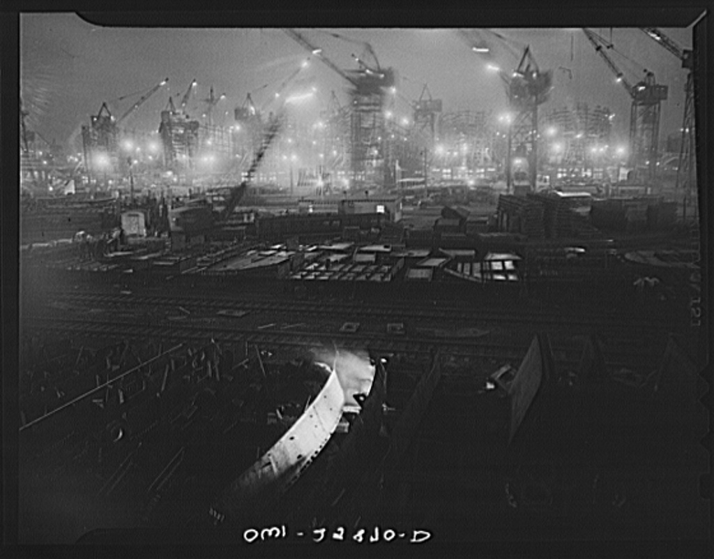 Bethlehem-Fairfield shipyards, Baltimore, Maryland. The shipways at night with a welder in the foreground