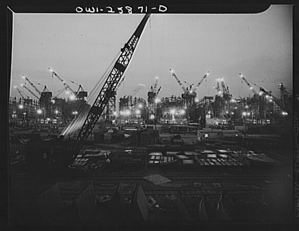 Bethlehem-Fairfield shipyards, Baltimore, Maryland. The shipways at night with a crane in the foreground