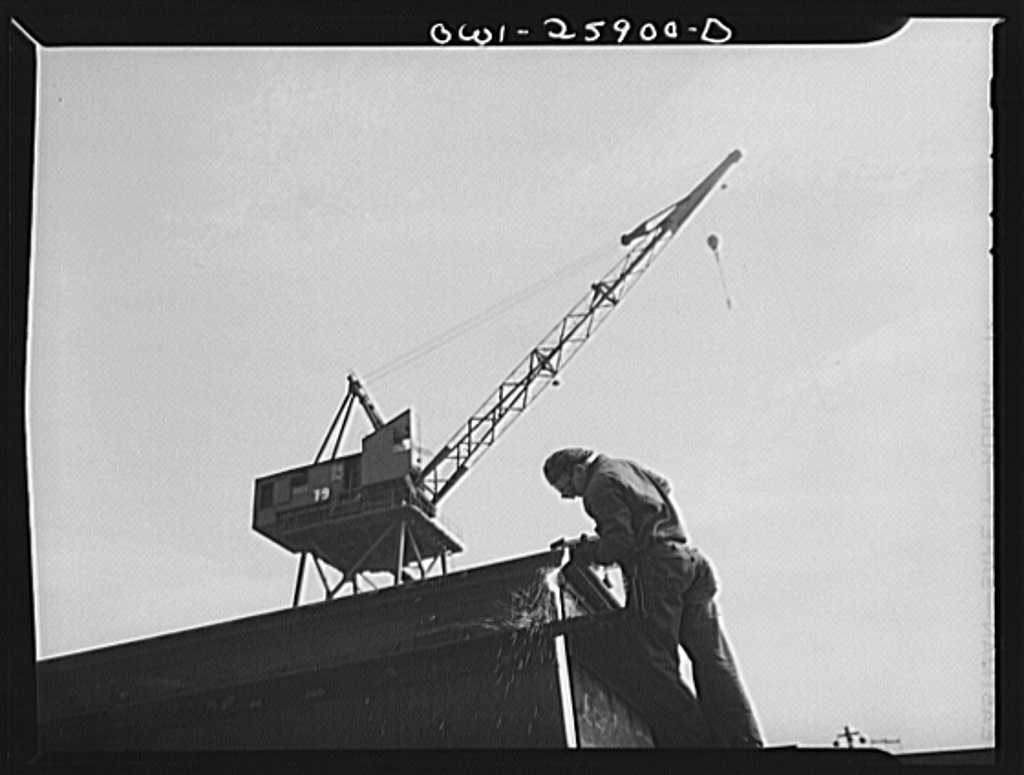 Bethlehem-Fairfield shipyards, Baltimore, Maryland. Welding the corner of steel section, with a crane in the background