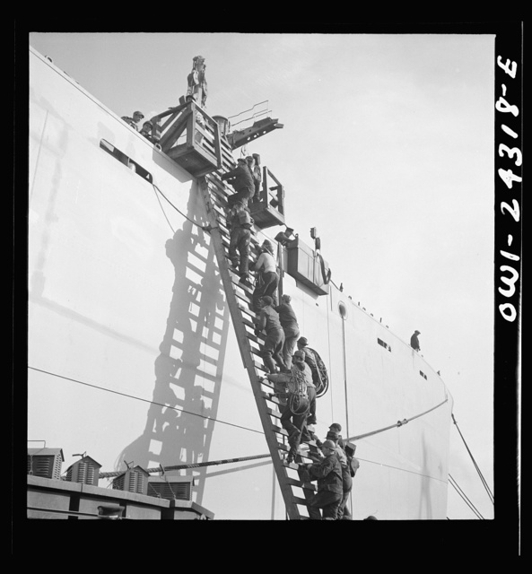 Bethlehem-Fairfield shipyards, Baltimore, Maryland. Workers ascending a ladder at the outfitting pier