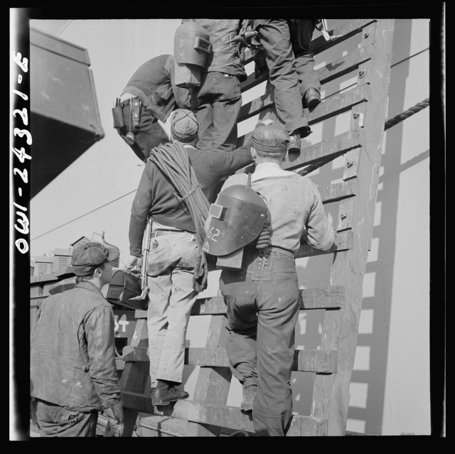 Bethlehem-Fairfield shipyards, Baltimore, Maryland. Workers on a ladder at the outfitting pier