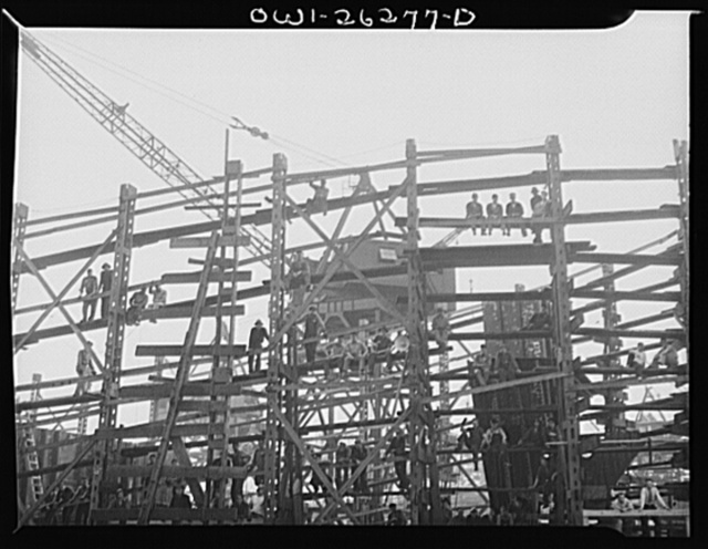 Bethlehem-Fairfield shipyards, Baltimore, Maryland. Workmen sitting on the scaffold watching the launching ceremony