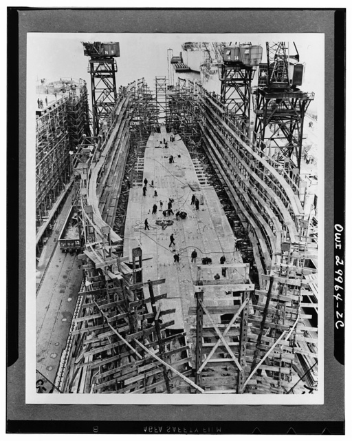 Bethlehem Fairfield shipyards, near Baltimore, Maryland. Constructing a Liberty ship. Ten hours after the laying of the first keelplate the bottom of the ship begins to form. Bottom shell plates are added which are bolted at first and will be riveted together later