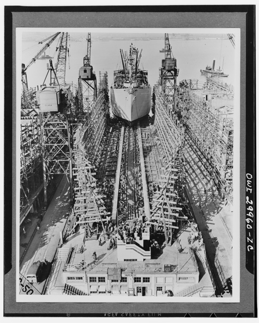 Bethlehem Fairfield shipyards, near Baltimore, Maryland. Construction of a Liberty ship. The ship sliding down the ways just twenty-four days after her keelplates were laid. It will take ten days longer to install furnishings. The ship weighs 3200 long tons and is known as a 10,500 ton cargo vessel