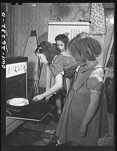 Buffalo, New York. Beverly Ann Grimm, eleven, examining her omelette. She is disappointed with the results, it puffed up too much without browning. She is a good cook. Pasty and Mary, her sisters, look on. Their mother, a twenty-six year old widow, is a crane operator at Pratt and Letchworth