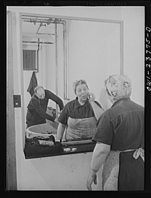 Buffalo, New York. Italian-American woman, grinder and hooker at the New York Car Wheel Company, powdering her nose. This concern has only recently hired women, and the women's locker room is still unfinished. A plumber can be seen in the background installing a sink. This situation is typical of many defense plants, especially in heavy industry
