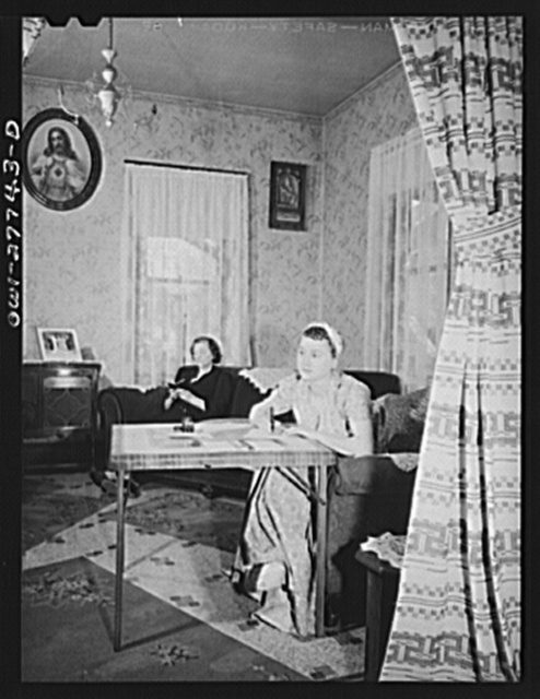 Buffalo, New York. Laura Ozaya writing to her husband, a corporal stationed in Arkansas. This is Sunday, and she has washed and set her hair. Her mother is reading a prayer book in the background. Laura works in the inishing department of Symington-Gould, makers of tank, ship and railroad parts. The Czayas are of Polish descent
