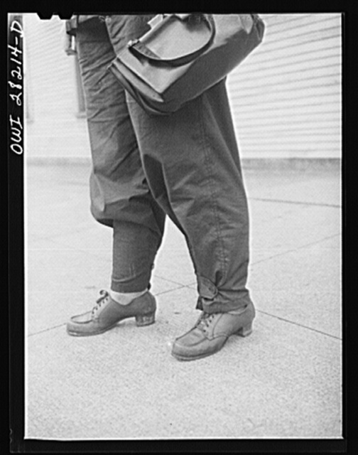 Buffalo, New York. Mrs. Grimm, a twenty-six year old widow with six children under twelve, works as a crane operator in a war plant. For work she wears slacks, which can be buttoned around, and safety shoes, which have inner metal plates in toes for protection from falling weights