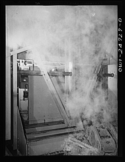 Buffalo, New York. Symongton-Gould, makers of tank, ship and railroad parts. Woman operating a charging machine. She works the machine by hand controls behind a partition, and has just dipped red hot metal into water, causing steam