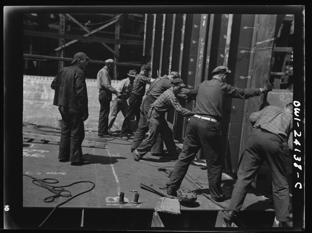 Building the SS Frederick Douglass. More than 6,000 Negro shipyard workers are employed at the Bethlehem-Fairfield shipyards, where the Liberty ship is being rushed to completion. The noted orator and abolitionist leader worked as a ship caulker in the vicinity of this yard before he escaped from slavery. Men setting bulkhead in place, running from tank deck to flat deck in aft of ship