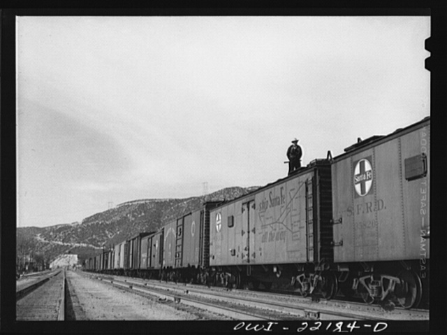 Cajon, California. Swing brakeman riding on top of the Atchison, Topeka and Santa Fe Railroad train. Brakeman ride the trains in this way during the entire descent from summit to San Bernardino