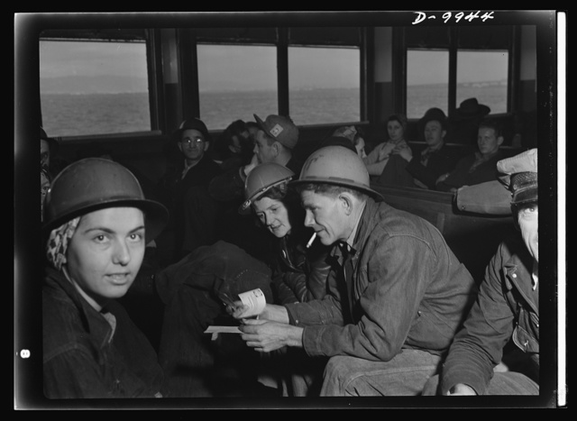 California shipyard workers. En route to the shipyards across the bay, tin-hatted San Francisco war workers have time for relaxation and discussion on the fourty-five minute ferry ride to the Richmond Shipbuilding Company yards