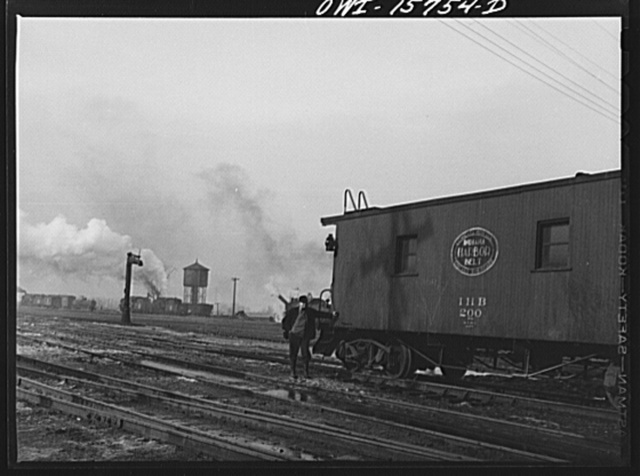Calumet City, Illinois. Conductor waiting beside his caboose in the yards of the Indiana Harbor Belt Railroad
