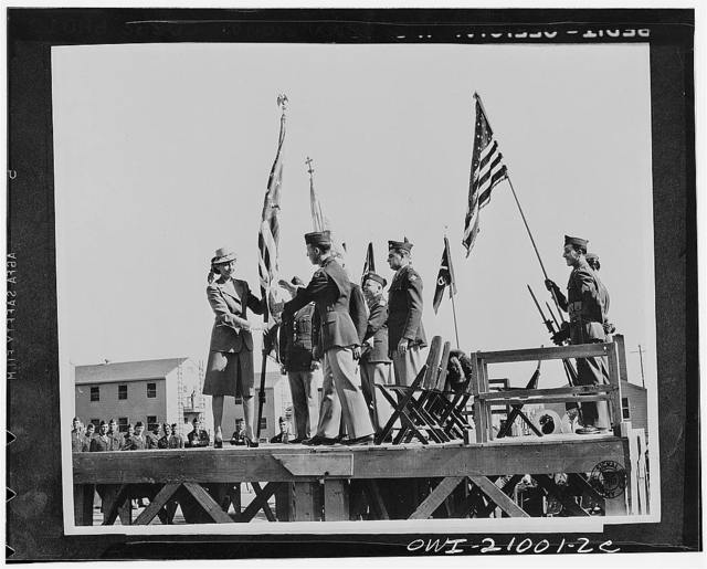Camp Carson, Colorado. The American flag is presented to Major Peter D Clainos, Commanding officer of the 122 Infantry Greek battalion by Mrs. Clainos on behalf fo the Greed-Americans of the Rocky Mountain region. The presentation was made at the battalion's activation ceremonies