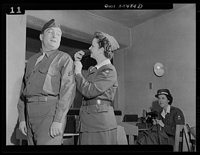 "Catching that stitch in time, Mrs. Viola Schlaegel of the American Women's Volunteer Service unit at Glendale, California does a good turn for Corporal Hugh B. Helm of Lexington, Kentucky. Members of the American Women's Volunteer Service ""Button Brigade"" meet at least twice weekly at the Army Air Force barracks in Glendale to do minor tailor work"