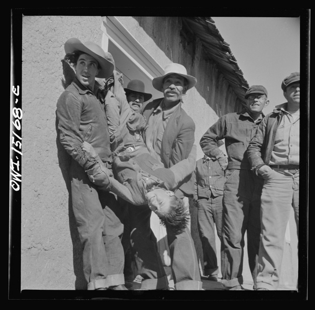 Chacon, Mora County, New Mexico. Idlers at the general store holding a small boy for the photographer