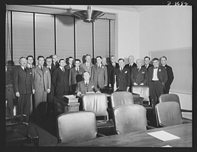 Charles E. Wilson, executive vice-chairman of the War Production Board (WPB), and staff. Standing, left to right: Arthur L. Hawley, assistant to Mr. Wilson; Carroll K. Shaw, executive officer; Ray C. Ellis, director of the Radio Division; T.P. Wright, director, Resources Controll Office, Aircraft Production Board; L.R. Boulware, Office of the Controller of Shipbuilding; M. Joseph Meehan, associate director, Office of Progress Reports; William B. Murphy, director of Facilities Division; William K. Frank, director, General Industrial Equipment Division; A.H. Bunker, director, Aluminum and Magnesium Division; John S. Chaffee, deputy director, Tools Division; R.L. Vaniman, director, Automotive Division; Curtis E. Calder, director general for operations; Ralph J. Cordiner, director general of War Production Scheduling; Captain J.O. Gawne, director, Shipbuilding Division; Francis M. Shields, director, Safety and Technical Equipment Supplies Division; Mordecai Ezekiel, assistant to Mr. Wilson; Fred Searls, Jr., director, Facilities Bureau; James N. Nicely, assistant to Mr. Searls