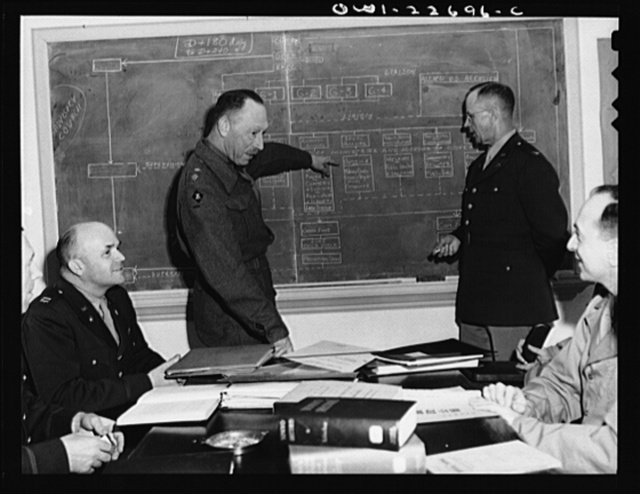 Charlottesville, Virginia. Meeting of a committee of ten studying the administration of occupied areas in the School of Military Government at the University of Virginia. The officer at left of the blackboard is Lieutenant Colonel R.J. Weale, of the British Army