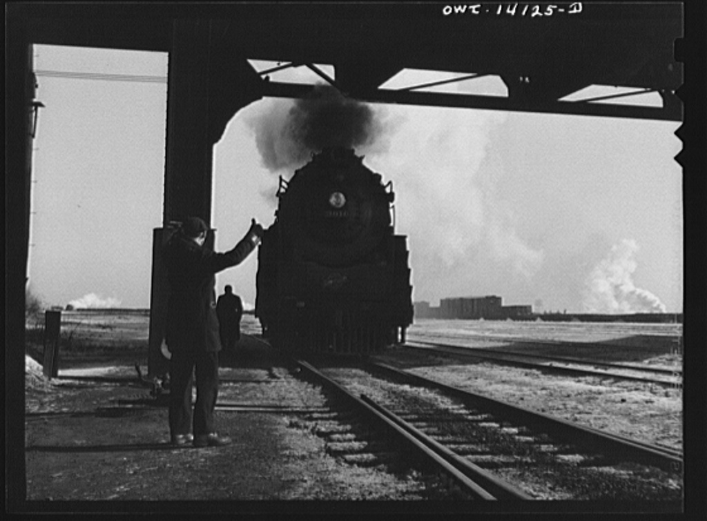 Chicago, Illinois. Conductor giving the engine the OK sign when he arrives after a trip from Clinton, Iowa. The train has been left in the yard and the engine is on its way to the roundhouse. Mr. Wolfsmith, the conductor, can now go home