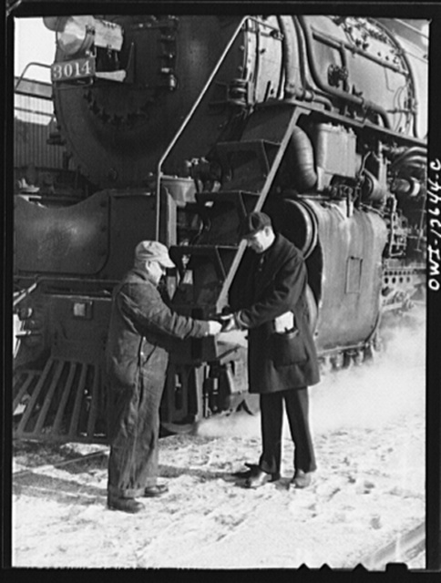 Chicago, Illinois. Conductor handling engineer copy of train orders before a Chicago and Northwestern Railroad freight train pulls out for Clinton, Iowa. Since the track between those points is under automatic train control, the engineer, in turn, hands the conductor the key to the automatic train control lock of the engine. The conductor will keep the key in the caboose until the train arrives at its destination