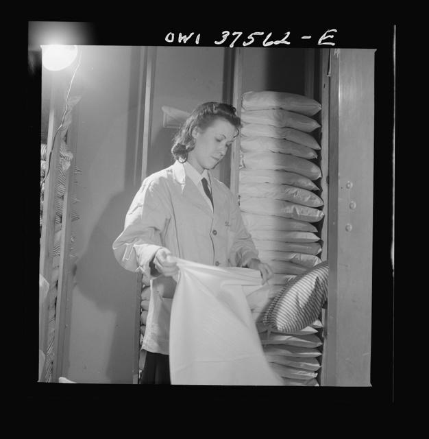 Cincinnati, Ohio. Pillow salesgirl putting clean covers on pillows