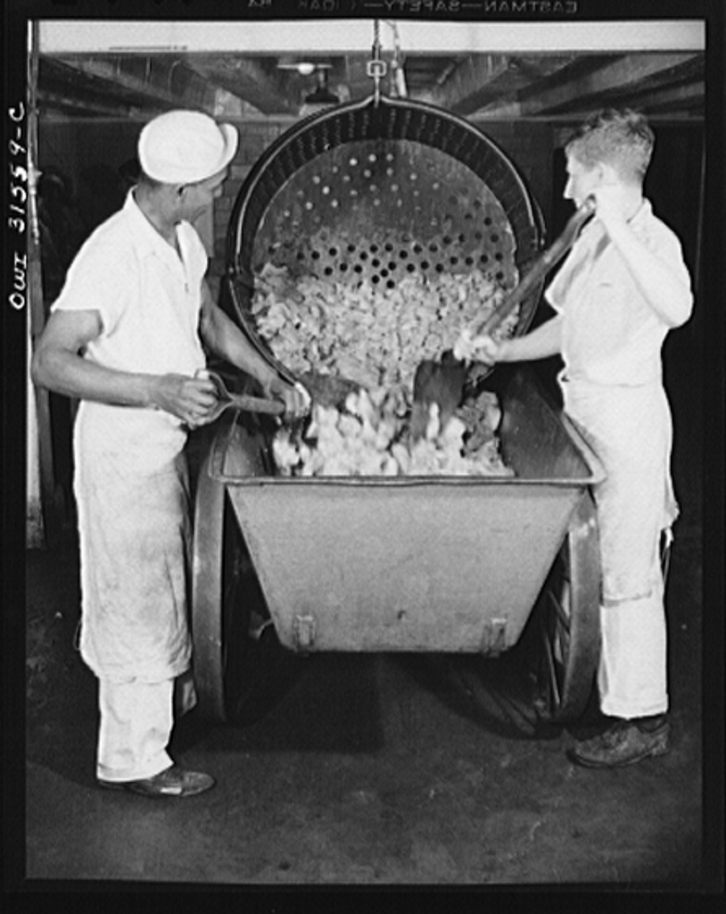 """Cincinnati, Ohio. Preparing canned pork (Russian: """"svinaia tushonka"""") for lend-lease shipment to the USSR at the Kroger grocery and baking company.  Removing pork from a container, after treating it for twenty percent shrinkage. Henderson Fuller, (left), age forty, used to do construction work"""