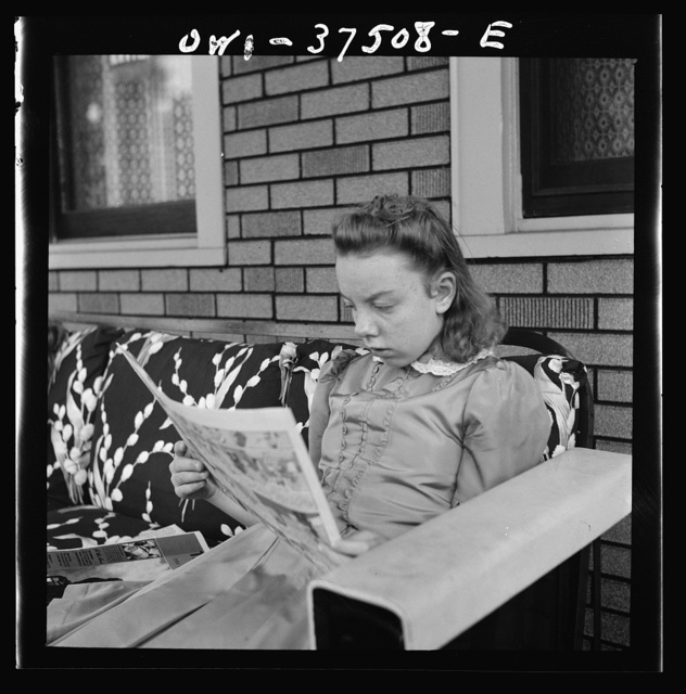 Cincinnati, Ohio. The eldest daughter of Bernard Cochran, a Greyhound bus driver, reading the Sunday funnies on the porch
