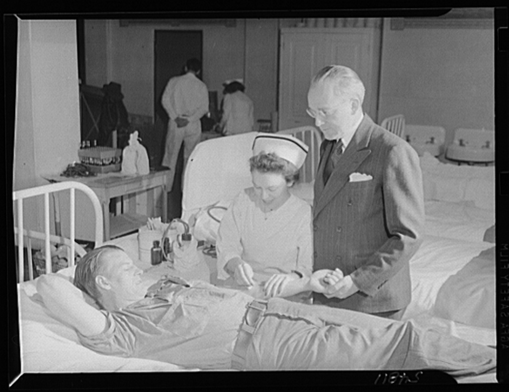 Clinton D. Duffy, warden of San Quentin, stands at a prisoner's bedside while Red Cross nurse Florence Aldrich prepares trhe young man for his donation. During the Red Cross mobile unit's visit, 150 men gave blood to the bank and more than twice that number volunteered but could not give because of lack of time and equipment