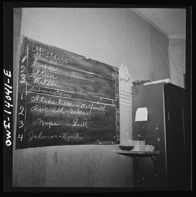 "Clinton, Iowa. Blackboard in the Disher rooming house for railroad workers. It lists the names and room numbers of the men. This enables the ""caller"" to find the men and wake them. If men come in very late and go out very early they simply enclose their fifty cents in one of the envelopes, write their name on it, and drop it in the slot in the little box in the corner"
