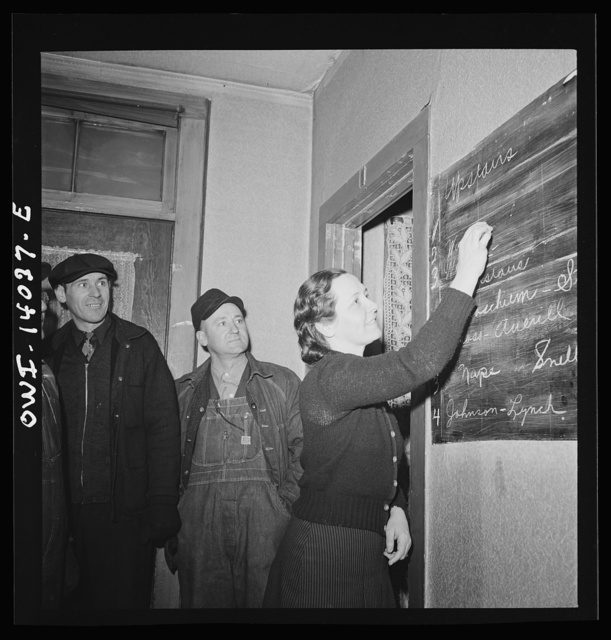 """Clinton, Iowa. Miss Lucille Disher, whose father was a railroad worker for forty years, runs a rooming house for railroad workers. Here she is assigning rooms to a crew that just came in. The men's names on the blackboard enable the """"caller"""" to find and wake them in the morning"""