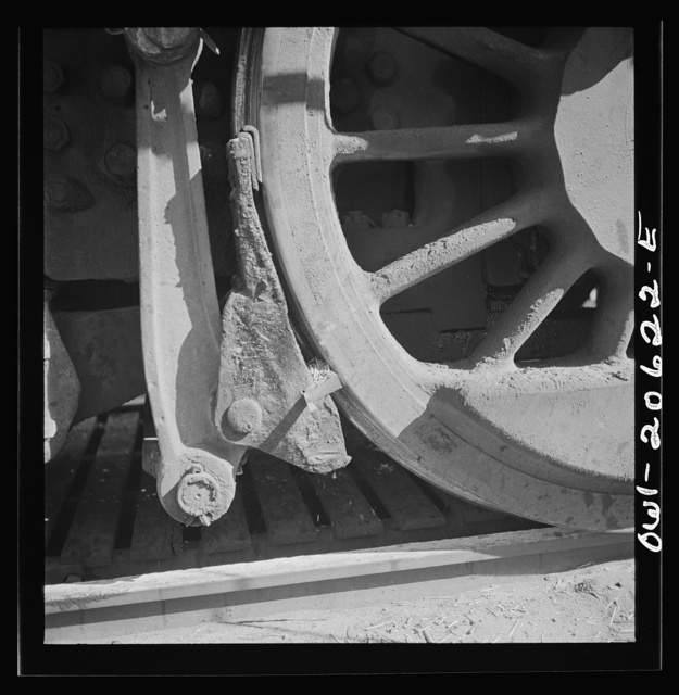 Clovis, New Mexico. Refacing the tires of a locomotive with a Ledgerwood apparatus. The locomotive is drawn down the rails by a cable, while cutting edges inserted in the brake shoes does the refacing in the Atchison, Topeka and Santa Fe Railroad shops