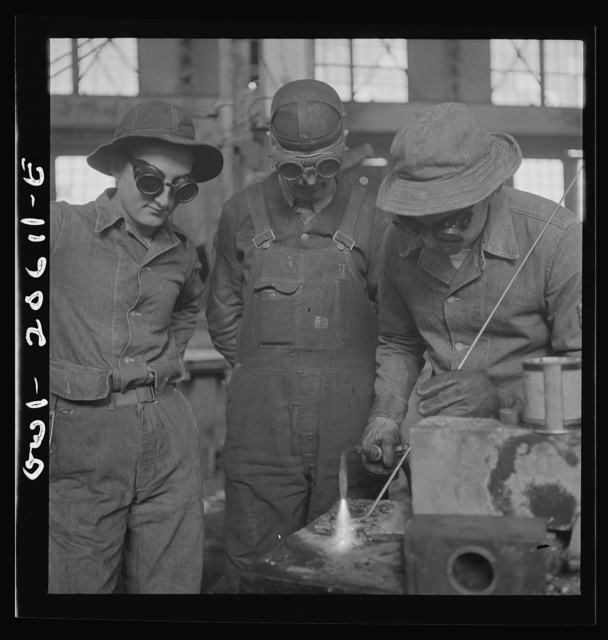 Clovis, New Mexico. Soldiers of the United States Army Railroad Battalion study welding at the locomotive shops in the Atchison, Topeka and Santa Fe Railroad. Left to right: Private Edward Dravis of Minnesota; Earl Weidinger, instructor and welder; and Sergeant Arthur Cannon of Indiana