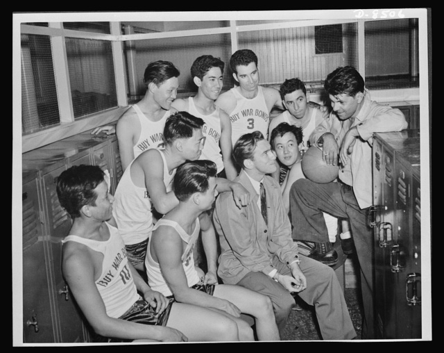 Coach Edwin Firiera, holding ball, gives his near pond team a pep talk in the locker room prior to their first league game. Seated with the players is assistant to the personnel officer at the Pearl Harbor Yard, Harry Brownell. This team is one of those composed of workers in the various shops at the navy yard