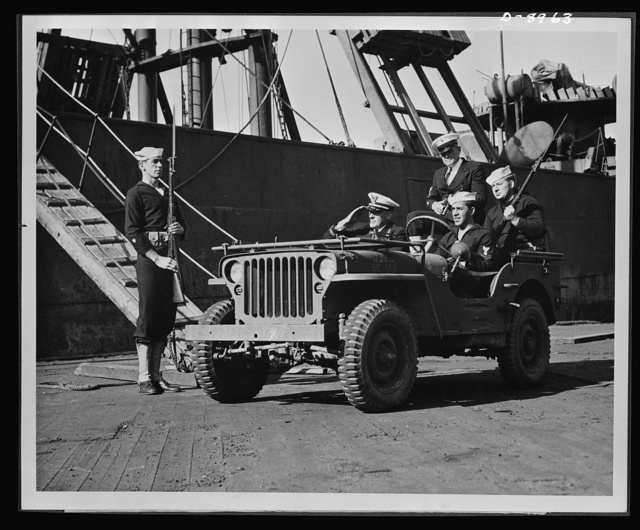 Coast Guard anti-saboteur patrol. A Coast Guard officer is shown at an East coast port with armed Coast Guardsmen in a jeep as he inspects the vigilant waterfront patrols that guard vital war supplies being shipped across. Valuable shipping must be protected on the piers as well as on the shipping lanes