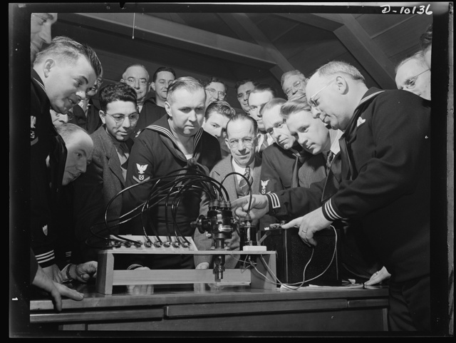 Coast Guard Auxiliary. Guardians of inland waters. Coast Guard Auxiliary members meet once a week for instruction. Here Harry Whitten, a Boston automobile distributor (right) gives instructions to fellow reservists in the workings of the ignition system of a marine engine