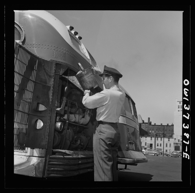 Columbus, Ohio. Randy Pribble, a bus driver for the Pennsylvania Greyhound Lines, Incorporated, putting water into a bus before taking it out on a run