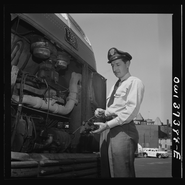 Columbus, Ohio. Randy Pribble, a bus driver for the Pennsylvania Greyhound Lines, Incorporated, checking the oil in a bus before taking it out on a run