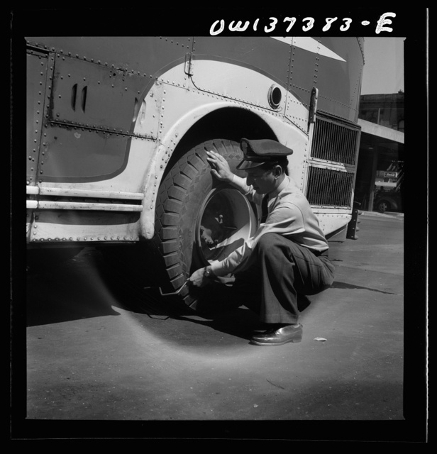 Columbus, Ohio. Randy Pribble, a bus driver for the Pennsylvania Greyhound Lines, Incorporated, checking tires on a bus by thumping them before taking it out on a run. Since there are two tires on the back, the sound is the best way of telling if one of them is flat