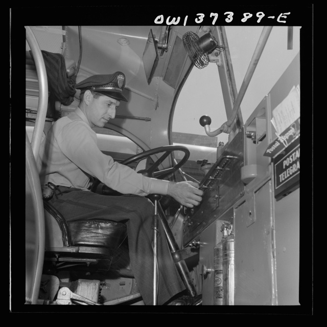 Columbus, Ohio. Randy Pribble, a driver for the Pennsylvania Greyhound Lines, Incorporated, checking the lights on a bus before taking it out on a run