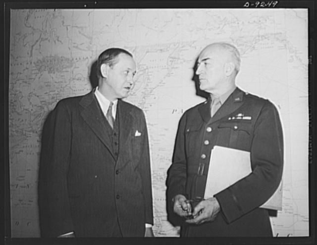 Combined Munitions Assignments Board. Chairman Harry Hopkins, of the Combined Munitions Assignments Board, confers with Major General J.H. Burns, executive officer of the board, before a huge world map at the board's conference room in Washington