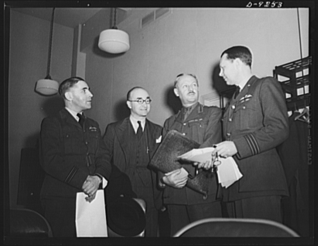 Combined Munitions Assignments Board. Staff members of the Combined Munitions Assignments Board discuss military matters at weekly meetings in Washington. Left to right are: Lieutenant M.V. Stewart (British); Mr. E.A. Seal (American); Brigadier L.F.S. Dawes (British); and Wing Commander T.E.H. Birley (British)