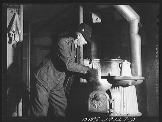 Conductor George E. Burton building a fire in the stove of the caboose on the Atchison, Topeka and Santa Fe Railroad enroute to Chillicothe, Illinois