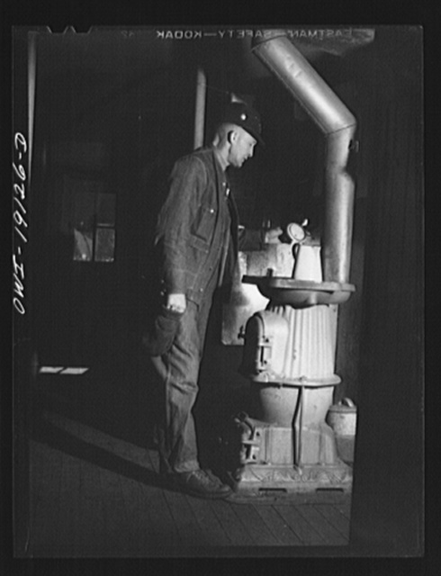 Conductor George E. Burton heats some coffee on the stove in the caboose on the Atchison, Topeka and Santa Fe Railroad enroute to Chillicothe, Illinois