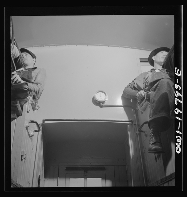 Conductor (right) and brakeman, in their places in the cupola of the caboose on the Atchison, Topeka, and Santa Fe Railroad between Argentine and Emporia, Kansas. On the wall between them is the air gauge showing the amount of air brake pressure in the train