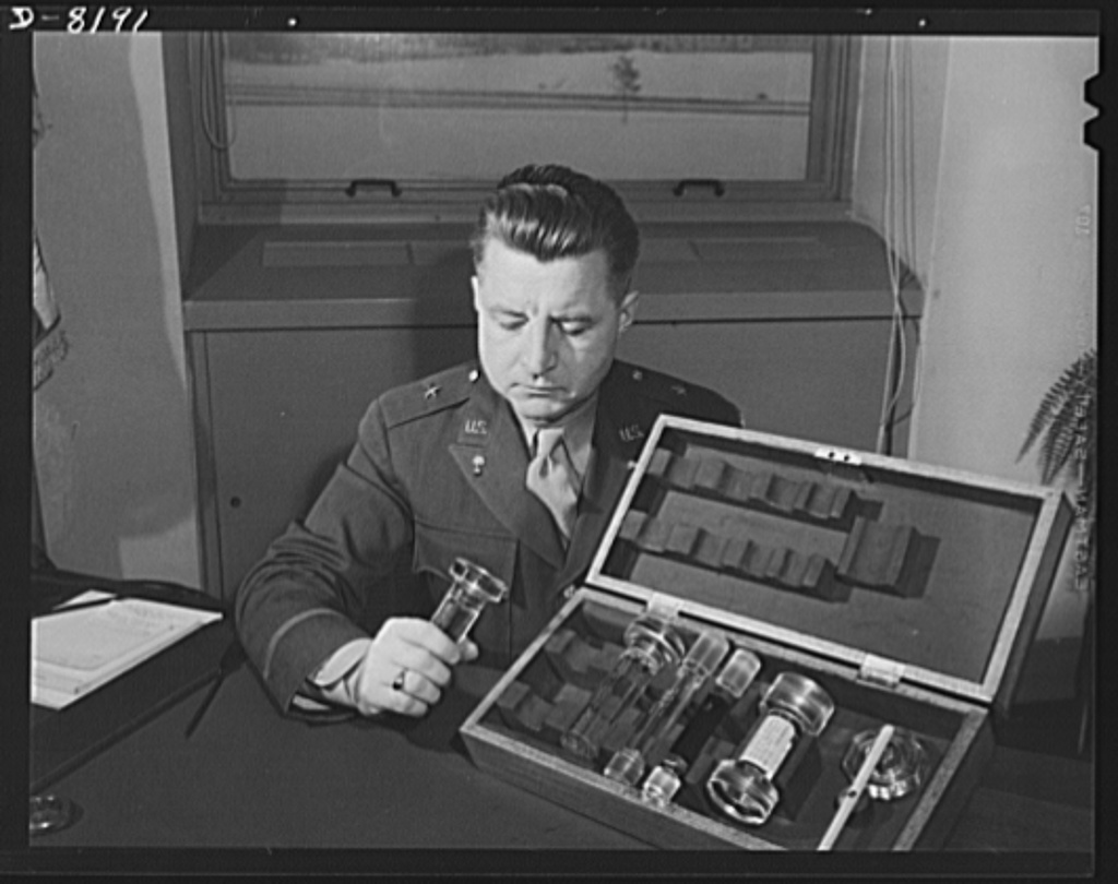 Conservation. Glass gauges replacing steel. Brigadier General H.F. Safford, Chief of Production Service Branch, Ordnance Department, examines an exhibit of standard types of new glass gauges which replace steel gauges at the Frankford Arsenal. Glass gauges are lighter and cheaper than steel, permit greater visibility in inspection, are not as much affected by room temperatures and heat of operators' hands, are not corroded by perspiration, need no protection against rusting, do not acquire burrs that would change the effective sizes. They can save the annual use of 250 tons of critical tool steel in government arsenals alone