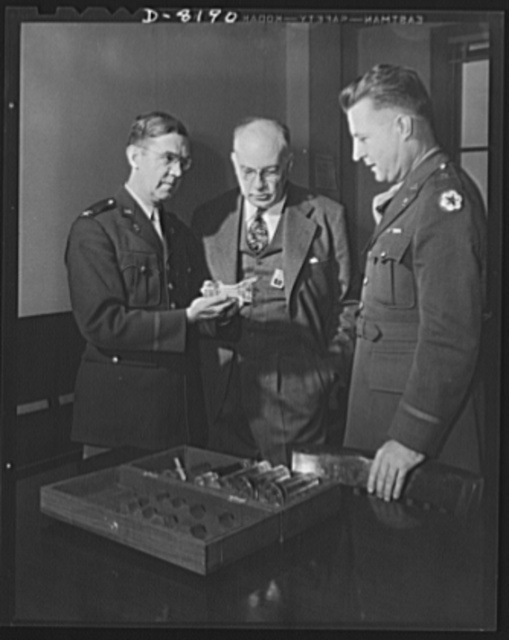 Conservation. Glass gauges replacing steel. Colonel H.B. Hambleton, Chief of Army Ordnance's Gage Section explains the virtues of a glass plug gauge to Mr. Thornton Lewis and Brigadier General H.F. Safford (left to right).  Glass gauges are lighter and cheaper than steel, permit greater visibility in inspection, are not as much affected by room temperatures and heat of operators' hands, are not corroded by perspiration, need no protection against rusting, do not acquire burrs that would change the effective sizes. They can save the annual use of 250 tons of critical tool steel in government arsenals alone