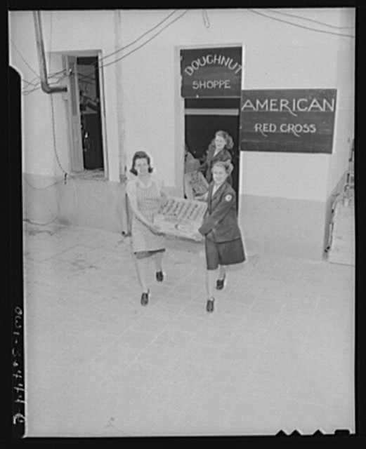 Constantine (vicinity), Algeria. A Red Cross girls carrying fresh doughnuts from an improvised kitchen to waiting clubmobile units which will carry doughnuts and coffee out to for bombers' crews who have just returned from a long mission